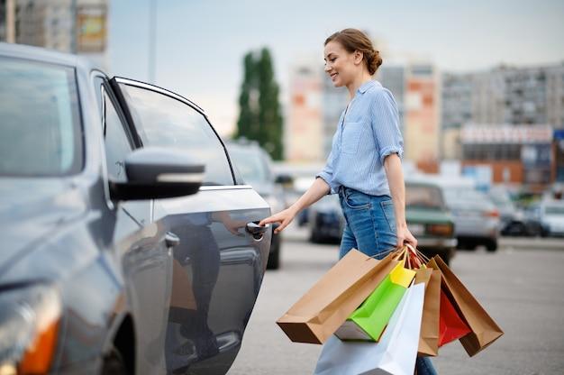 Женщина кладет свои покупки в машину на рыночной стоянке. счастливый клиент, несущий покупки из торгового центра, автомобили на заднем плане