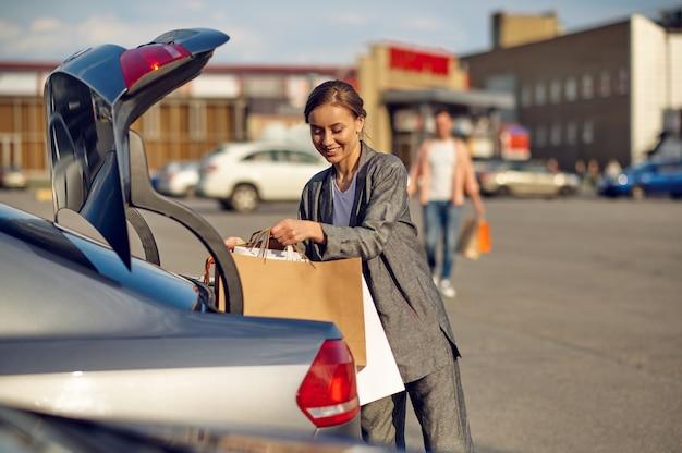 Женщина кладет свои покупки в багажник на парковке