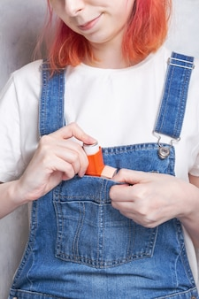 Woman puts an inhaler in pocket to treat asthma. world asthma day. concept of allergy care