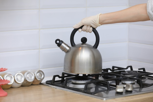 Woman puts a kettle on the kitchen in gloves on gas stove. stovetop whistling kettle in hand. selective focus