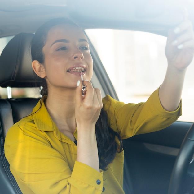女性は口紅をつけ、車の中に座っています。