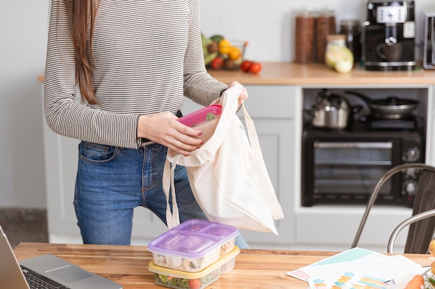 Woman puts lunch boxes in bag