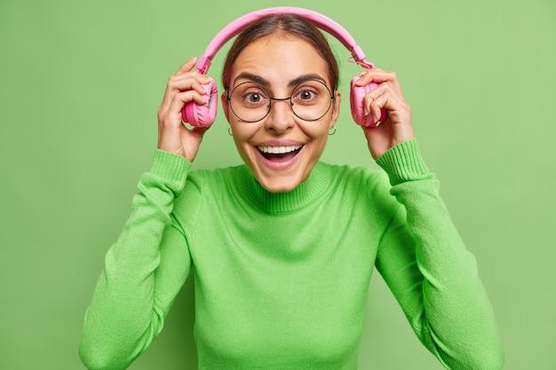 여자는 헤드폰을 끼고 즐겁게 오디오 트랙을 듣습니다. 행복한 분위기는 둥근 안경과 터틀넥을 녹색으로 착용합니다