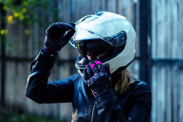 Женщина надевает мотоциклетный шлем и застегивает застежку
