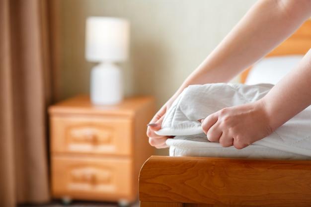 女性はマットレスの角に新しいマットレスパッドを置きます。自宅やホテルのベッドリネン。シートは柔らかく清潔な白いマットレスに着用されています。寝室のインテリアの汚れや洗ったリネンのマットレスパッドからの保護。