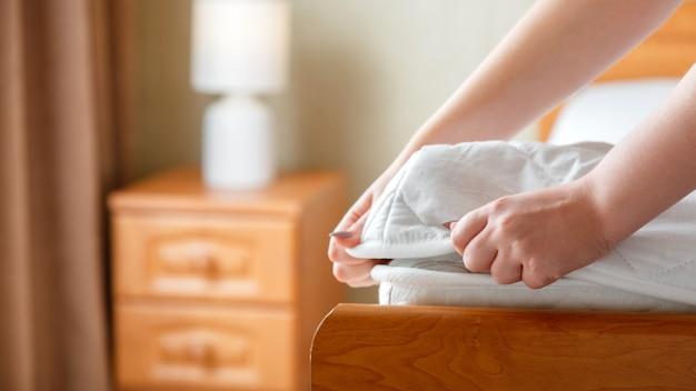 女性はマットレスの角に新しいマットレスパッドを置きます。自宅やホテルのベッドリネン。シートは柔らかく清潔な白いマットレスに着用されています。寝室の汚れで洗われたリネンマットレスパッドからの保護。長いウェブバナー。