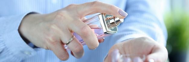 여자는 그녀의 손목에 향수를 넣습니다. 향수 개념의 올바른 사용
