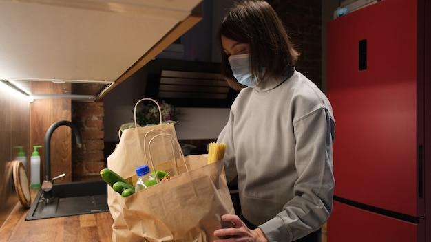 Женщина кладет пакеты с продуктами на стол и снимает маску дома