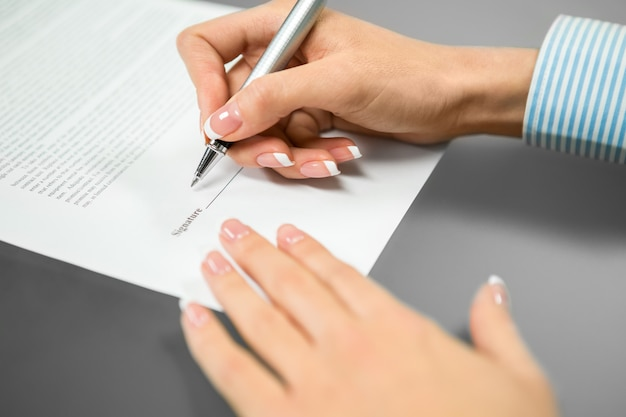 Woman puts a signature. the last signature needed. read and sign. everything is understood.