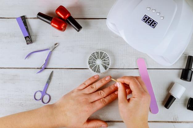 女性は銀のラインストーンを爪に置きます。ジェルマニキュアを作ります。