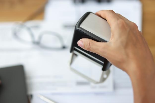 女性は公証人と弁護士の概念のオフィスサービスで文書にスタンプを押します