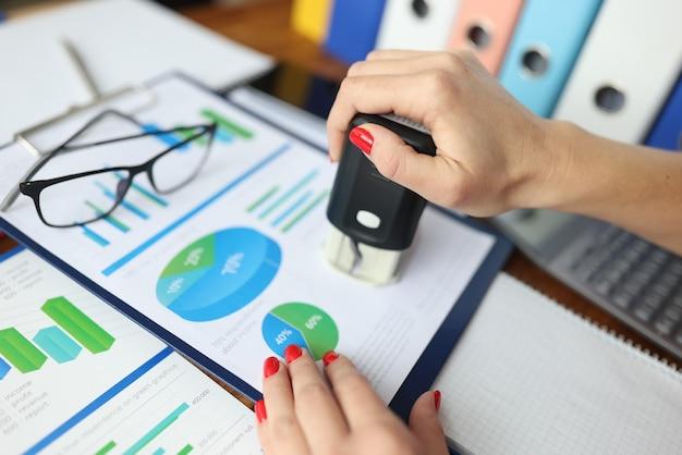 Женщина ставит печать на документы с коммерческими показателями