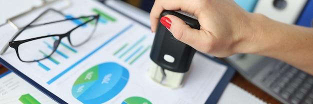 Женщина ставит штамп на документы с коммерческими показателями.