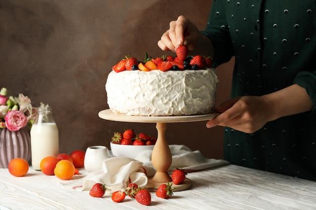 Woman puts strawberry on berry cream cake. delicious dessert