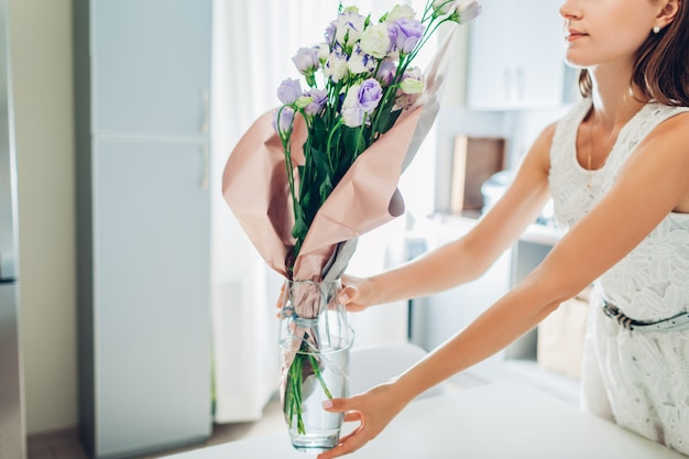 Woman puts vase with flowers. housewife taking care of coziness in kitchen. modern kitchen design