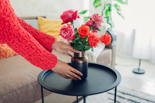 Woman puts vase with flowers roses on table, housewife taking care of coziness in apartment