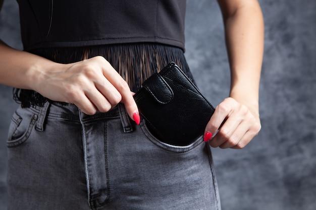 여자는 그녀의 주머니에 지갑을 넣습니다