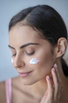 Женщина наносит ежедневный крем на щеки