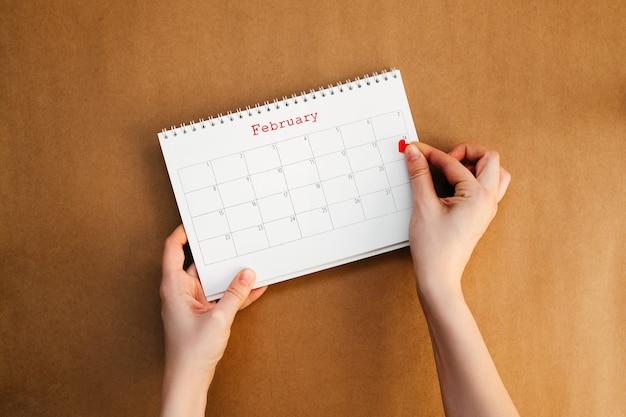 バレンタインデーにカレンダーにハートのステッカーを貼る女性。