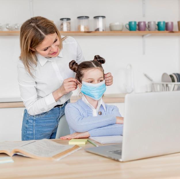그녀의 딸에 의료 마스크를 퍼 팅하는 여자