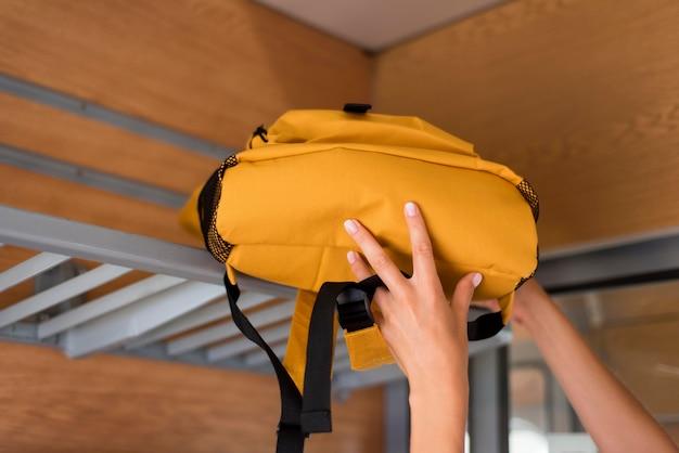 Woman putting backpack on train rack