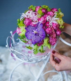 Woman putting a bouquet inside white wedding accesory