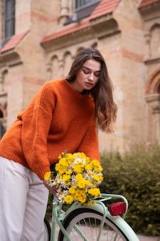 자전거에 꽃의 꽃다발을 퍼 팅하는 여자