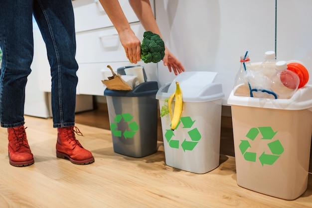 Woman putting broccoli in the garbage bin