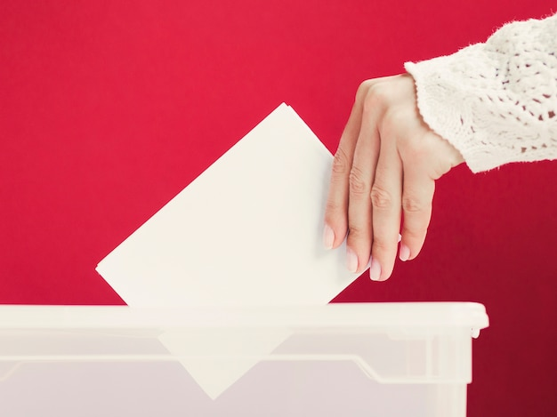Woman putting a card mock-up in a box for election