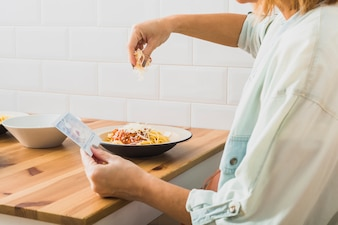 Woman putting cheese on food