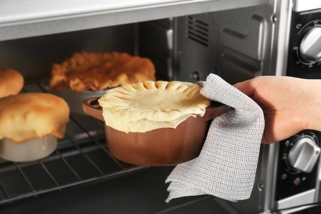 チキンポットパイをオーブンに入れる女性