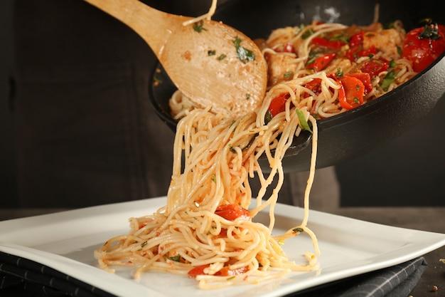 Женщина кладет куриные спагетти на тарелку