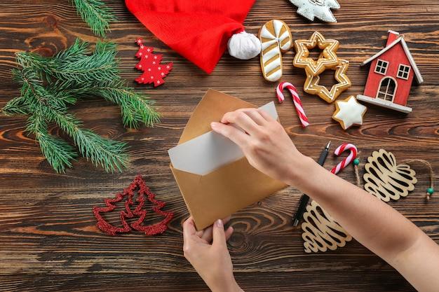 나무 테이블에 봉투에 크리스마스 편지를 넣어 여자