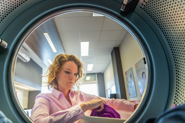 Woman putting clothes in a dryer in a public laundry