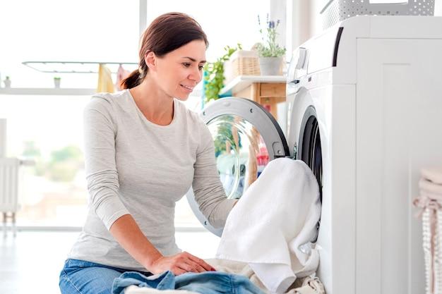 Женщина кладет одежду в стиральную машину в светлой прачечной
