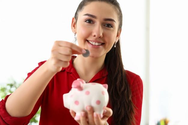 Женщина кладет монету в копилку, инвестиции