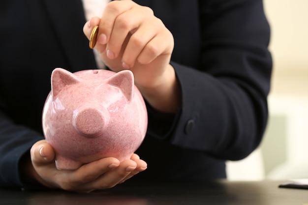 貯金箱にコインを入れる女性、クローズアップ。お金の節約の概念