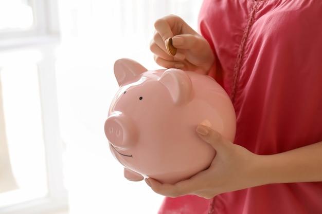 屋内の貯金箱にコインを入れる女性。お金の節約の概念