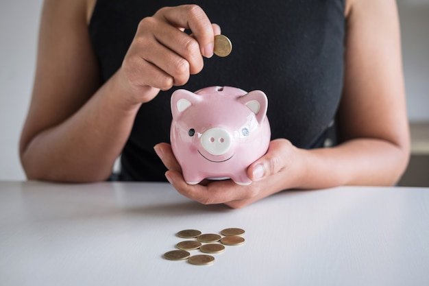 Woman putting coin in pink piggy bank for step up growing to profit and saving with piggy bank