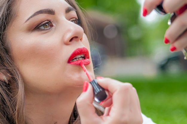 Woman putting, correcting red lipstick lip gloss. beautiful stylish brunette woman correct make up
