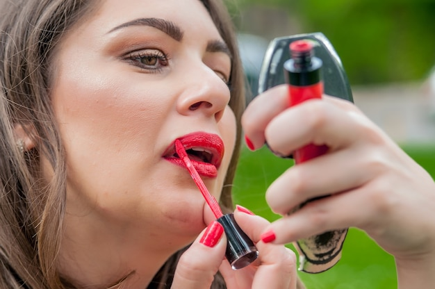 Woman putting, correcting red lipstick lip gloss.