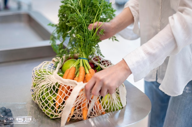 Женщина кладет продукты в сумку многоразового использования