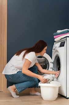 Woman putting dirty clothes in the washing machine