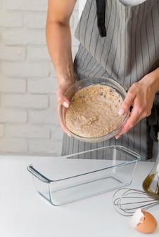 Женщина ставит тесто в форму для торта