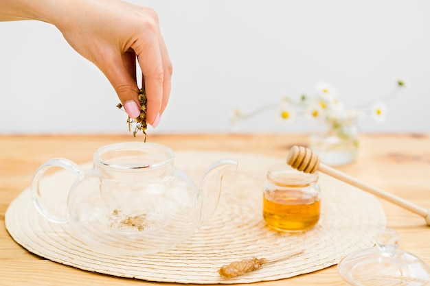 Woman putting dried herbs in empty teapot