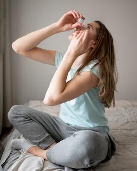 目の痛みのための目薬を置く女性