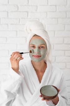 Donna che mette sulla vista frontale del trattamento del viso