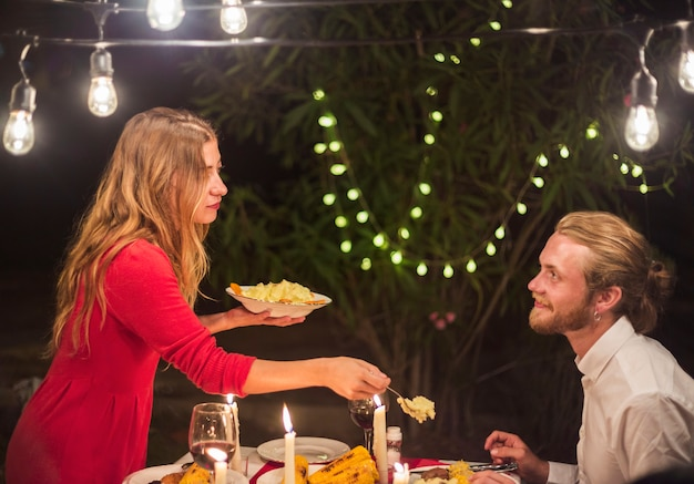 Woman putting food on plate of man