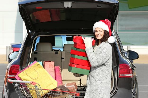 Женщина кладет подарки в багажник автомобиля на открытом воздухе