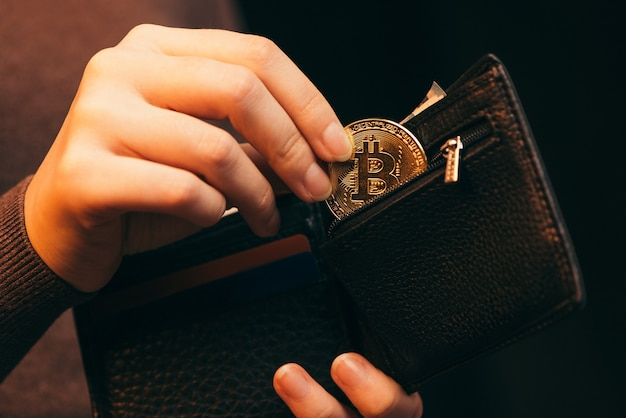 Woman putting golden bitcoin into her wallet on light background, closeup